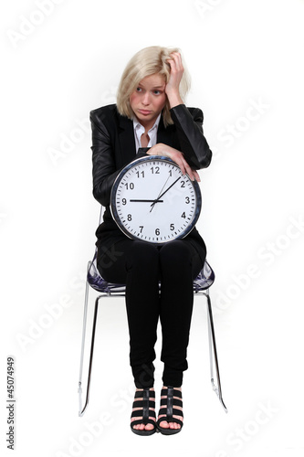 Depressed businesswoman with a clock