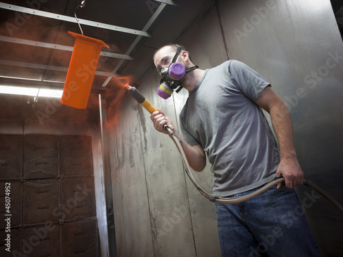 """USA, Utah, Orem, man using paint spray gun"""
