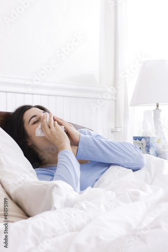 """USA, Utah, Orem, young woman sneezing in bed"""