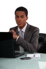Young businessman sat at his desk