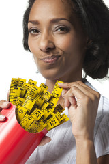 Mid adult woman holding container with mini tape measures instead of french fries