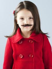 """Girl (6-7) in red coat wearing fake mustache, portrait"""