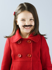 """Girl (6-7) in red and fake mustache smiling, portrait"""