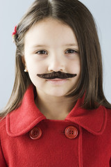 Studio portrait of girl (6-7) wearing fake moustache