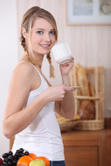 Woman stood in the kitchen holding mug and saucer