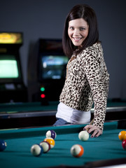 """""""USA, Utah, American Fork, young woman standing in playroom with pool cue behind her back"""""""