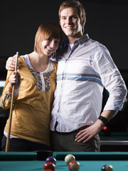 """USA, Utah, American Fork, young couple standing behind pool table"""