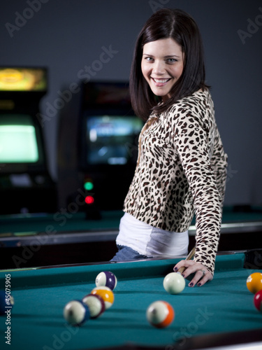 """USA, Utah, American Fork, young woman standing in playroom with pool cue behind her back"""