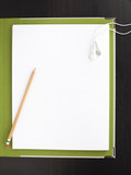 """Studio shot of note pad, pencil and headphones"""