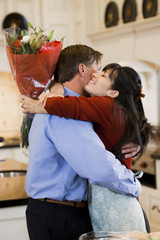 """USA, Utah, Alpine, mid adult woman greeting man at home"""