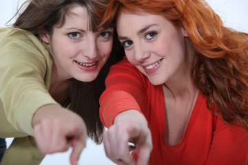 Two female friends pointing at the camera.