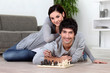 Couple sat at home playing chess