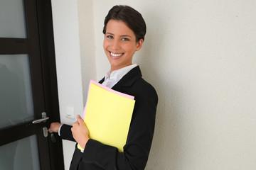 Female estate agent putting key in door