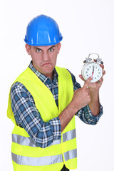 Angry builder pointing at alarm clock