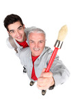 portrait of cute painter with senior instructor holding brush