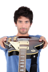 Man holding an electric guitar at arms length