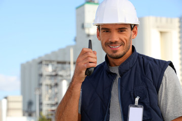 Construction worker speaking into his walkie-talkie