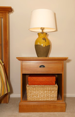 Wood furniture nightstand with lamp and bed.