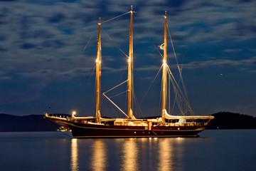 Wooden sailboat illuminated at night