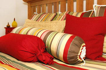 Bed and pillows in red, yellow and green stripes.