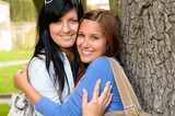 Mother and teen hugging outdoors relaxing smiling