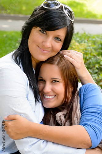 Mother holding teen daughter in her arms