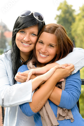 Teen and her mother embracing outdoors bonding