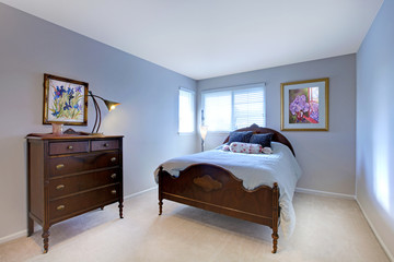 Blue bedroom with dark wood bed and dresser.