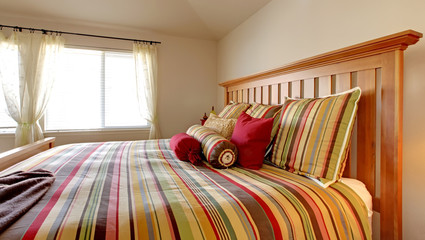 Large bed with beautiful bedding in stripe red, yellow
