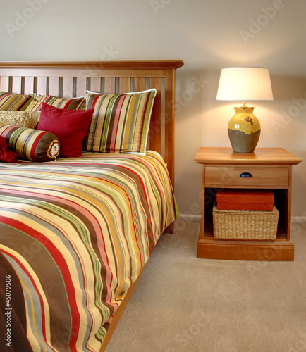 Wood bed and nightstand with stripes in red, yellow and green.
