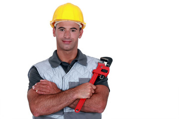 portrait of tradesman cross-armed holding adjustable spanner