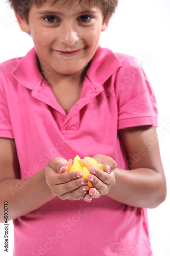 Little boy holding pieces of fruit