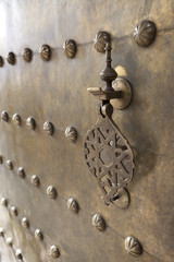 Metal doorknocker on brass door