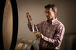 Vintner taking sample of white wine in cellar.