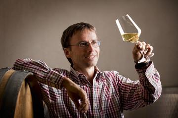 Pleased vintner looking at glass of white wine in cellar.