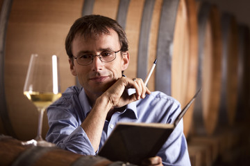 Pleased vintner looking at a glass of white wine in cellar.