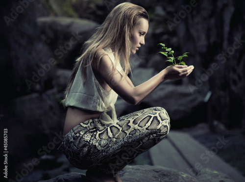 Beautiful young woman holding a plant - 45085703