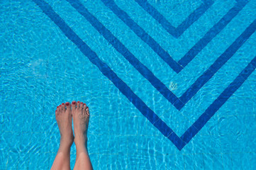 Woman's feet in a swimming pool