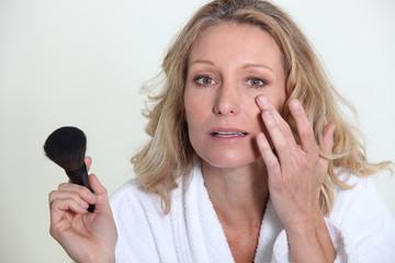 Blond woman applying makeup