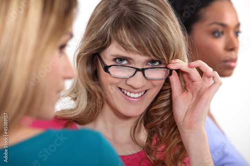 Young woman peering over her glasses