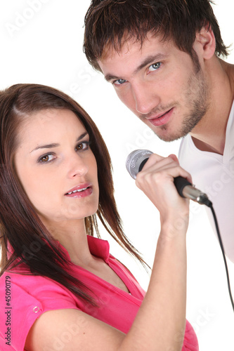 Young couple singing into a microphone