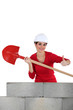 craftswoman holding a shovel and making a thumbs up sign
