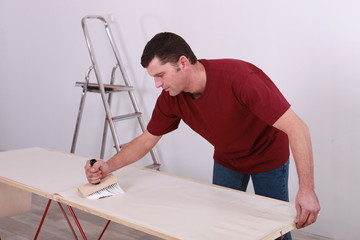 Man gluing wallpaper