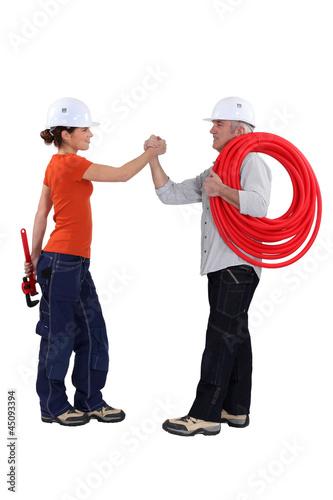Two handyman shaking hand.