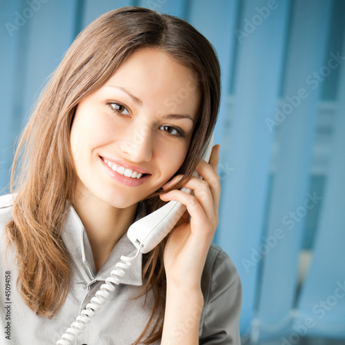 Young business woman with phone at office