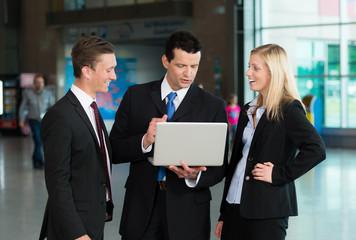 Redende Business-Gruppe mit Laptop