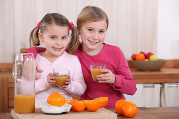 Two sisters drinking orange juice in kitchen