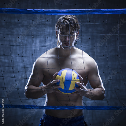 Studio shot of volleyball player standing behind net and holding ball