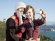 """USA, California, San Francisco, young couple taking pictures of themselves, Golden Gate Bridge in background"""