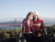 """USA, California, San Francisco, young couple sitting, Golden Gate Bridge in background"""